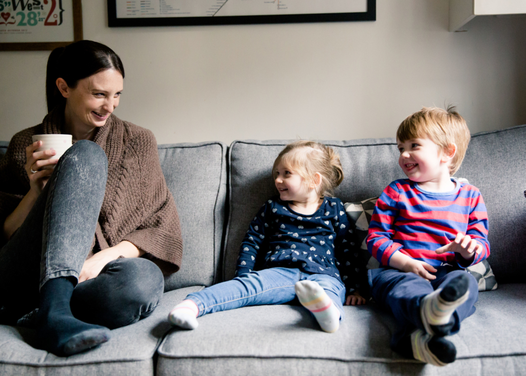Jo Britland sat on sofa from Little Writing Company with children printplaylearn